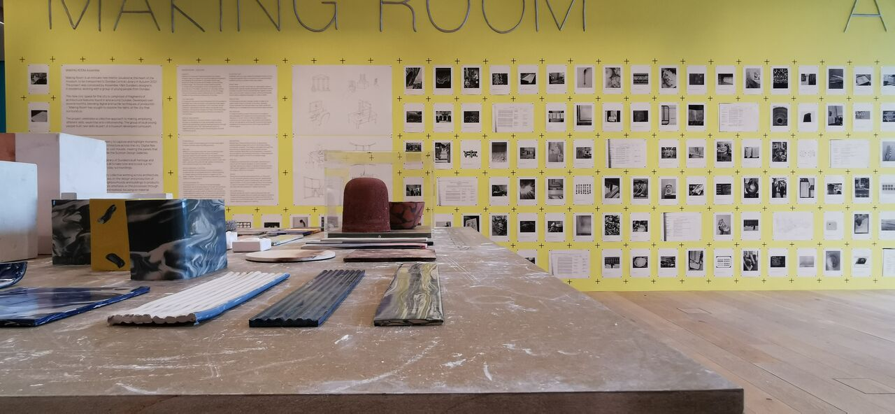 A table with several different materials on it, in the background the yellow wall has several photos of building attached to it.