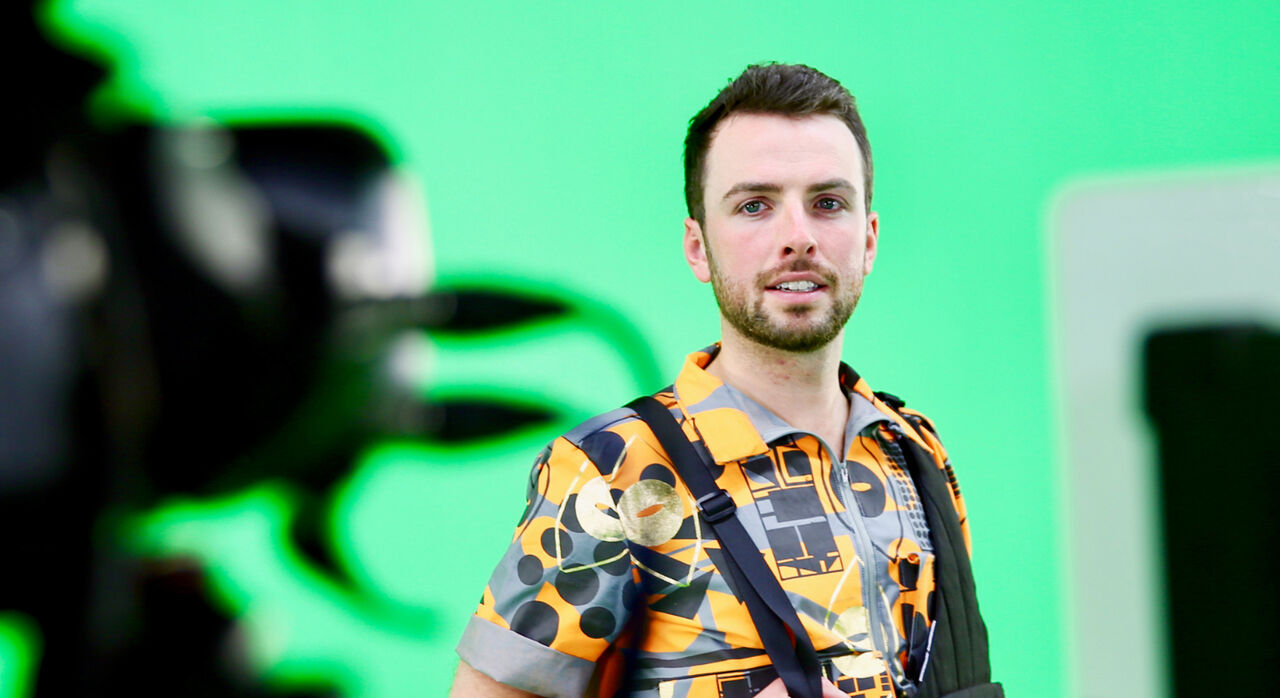 Shane Strachan wearing a patterned shirt, standing in front of a green screen