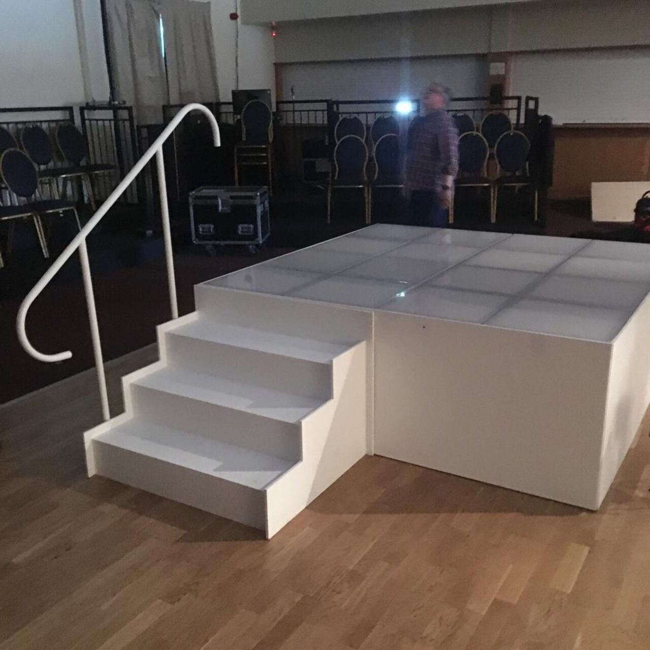 A small white stage with grey lines crossing the top.  A small white staircase with three steps leads up to the stage.  On the left hand side of the stairs is a white hand rail that curves down at each end.