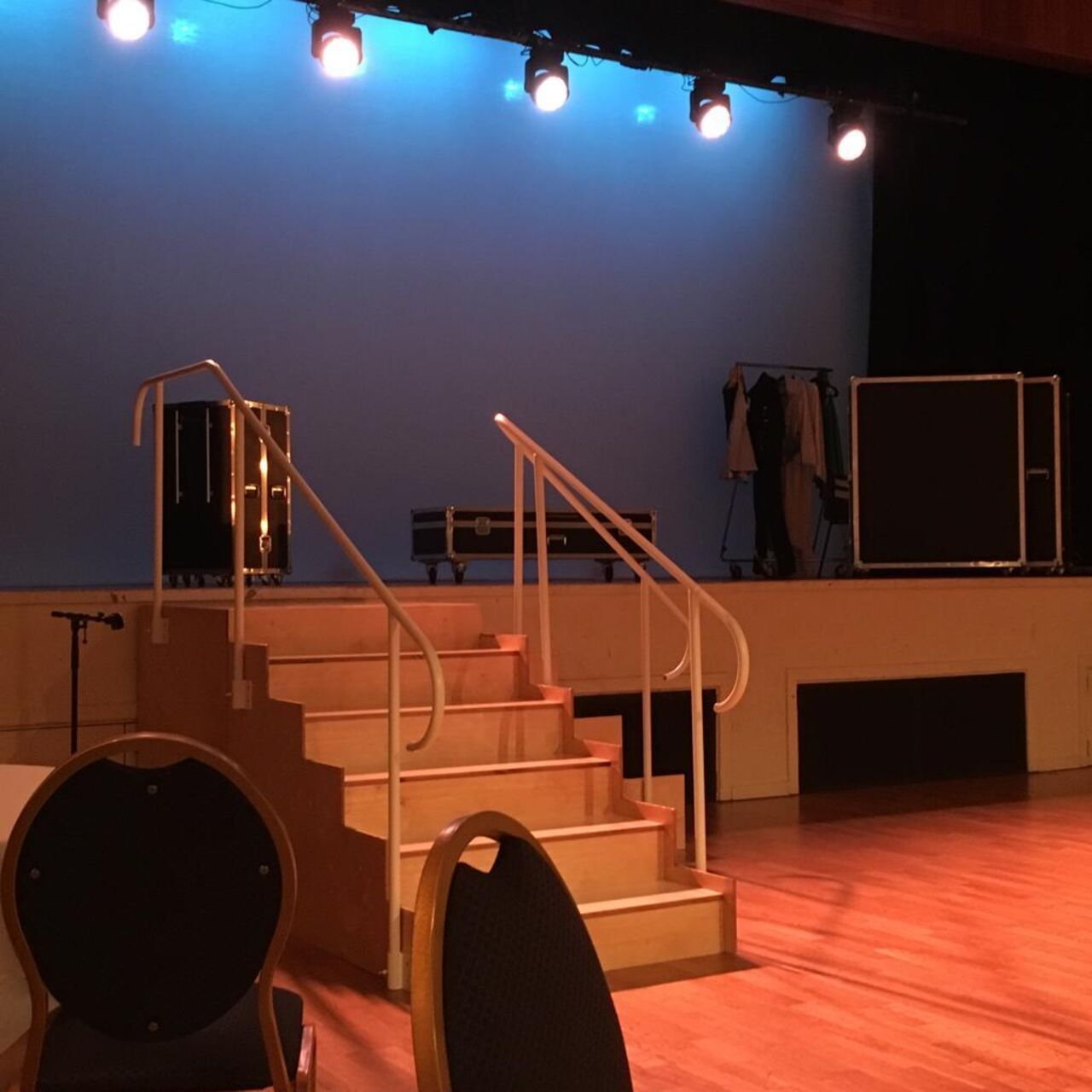 A stage with several flight cases and a clothes rail on it with lights facing out.  A set of wooden stairs leads from the stage to the wooden floor. The stairs have white handrails at either side which curves down at each end. On the right hand side there is a glimpse of a handrail from a second set of stairs leading down from the same place as the first.  In the foreground are two dining chairs.