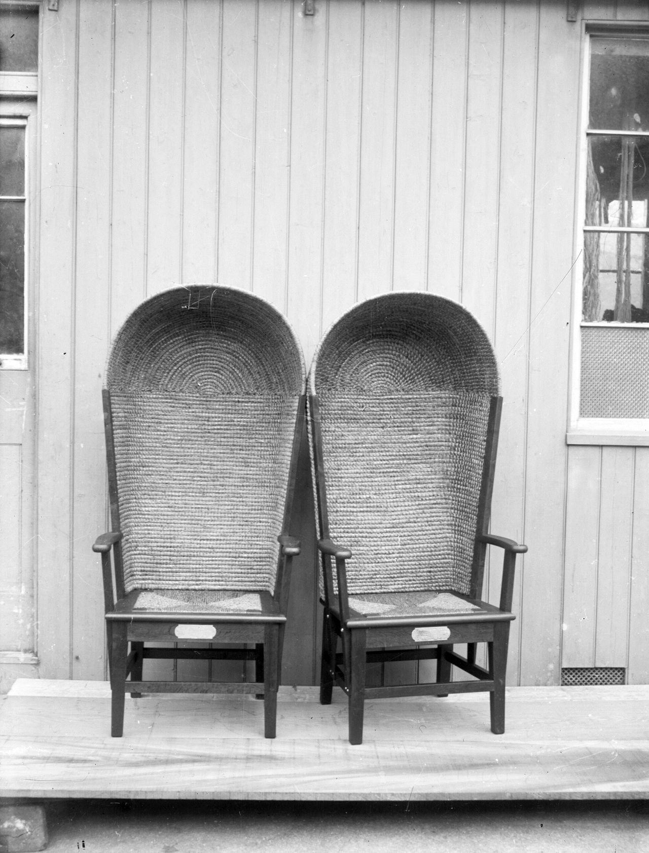 Black and white photo of two high-backed Orkney Chairs next to each other.