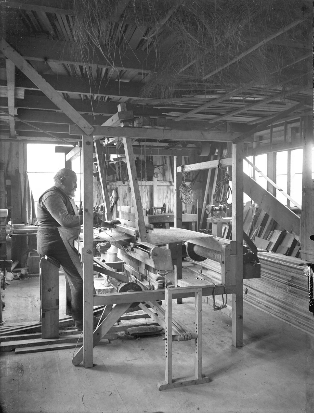Black and white photo of a man working in a studio.