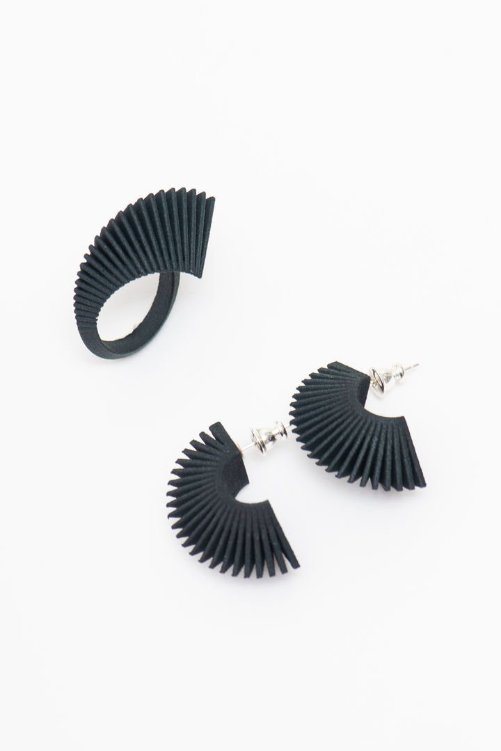 A black pair of earrings and a matching black ring. Both have deep geometric ridges evoking the museum building.