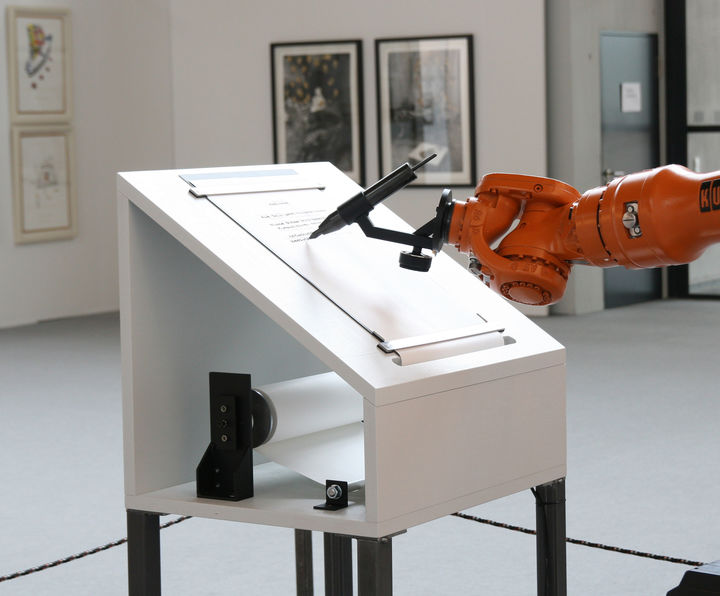 A sloped table on which sits paper and a robot arm holds a pen and writes on it.