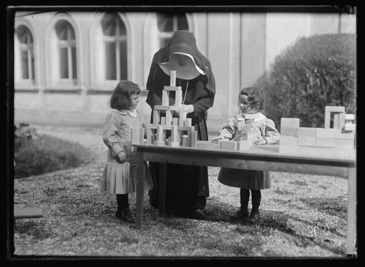 Archival photo of two children playing with blocks on a table, accompanied by a nun.