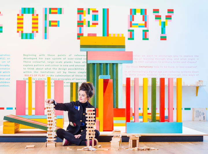 A woman sat on the floor playing with wooden planks in front of colourful huge wooden planks.