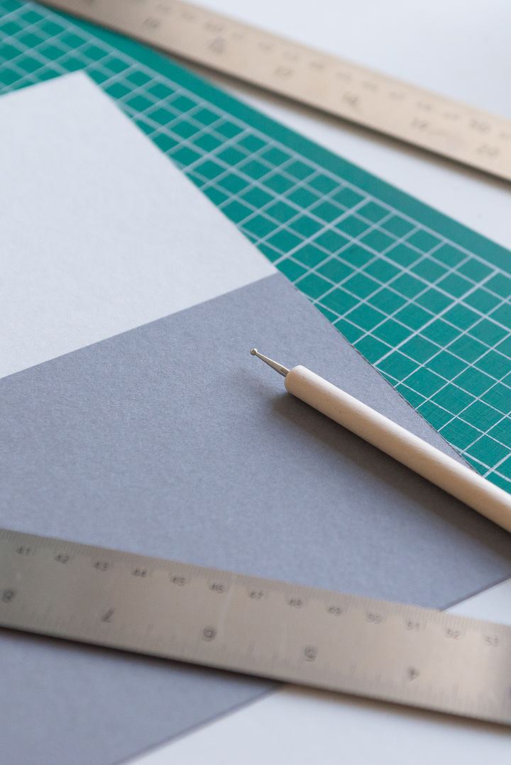 Paper lying on a cutting mat with a ruler and a scoring tool scattered across them.