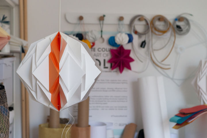 A folded, geometric paper lampshade in a studio, with hooks behind it on which are hung ropes and paper materials.