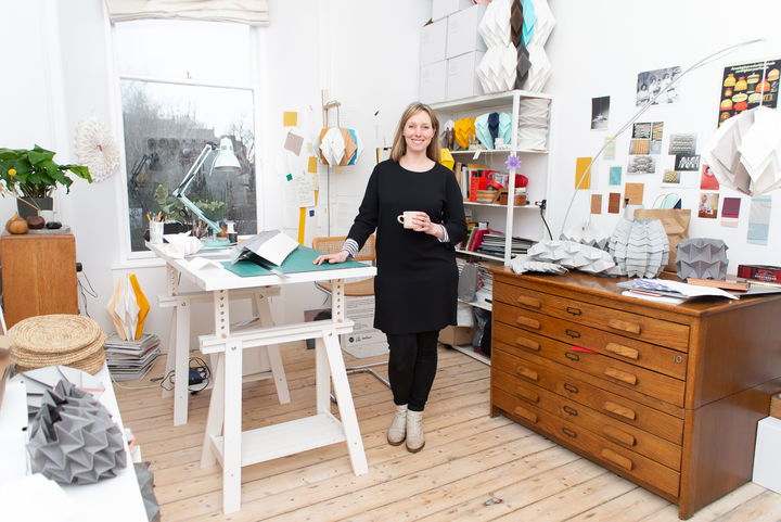 Kate standing next to her desk in a white, airy studio surrounded by paper creations.