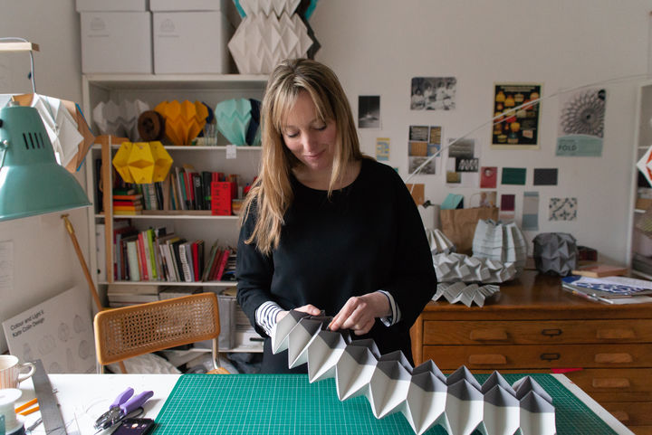Kate standing at her desk with a green cutting mat on it, folding grey and white paper into geometric shapes.