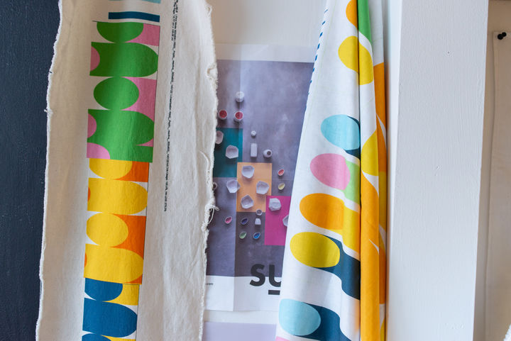 Two strips of fabric hangin in Laura's studio with brightly coloured shapes and patterns on them.