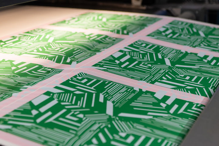 Large sheets of beautifully printed pattern (green with white lines) going through a large industrial printer.