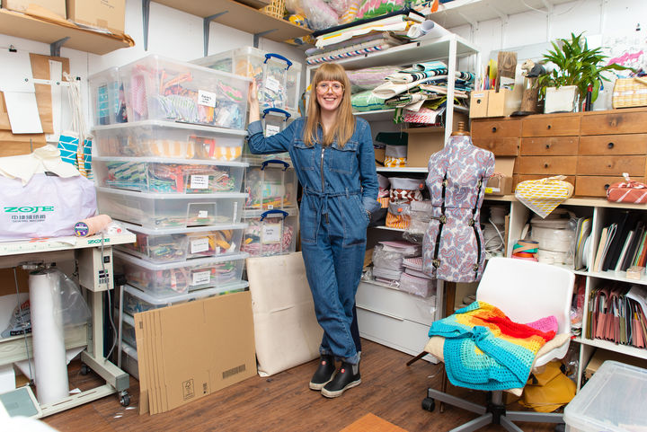 Laura Spring wearing a denim jumpsuit stood against boxes and shelves of materials and paints.