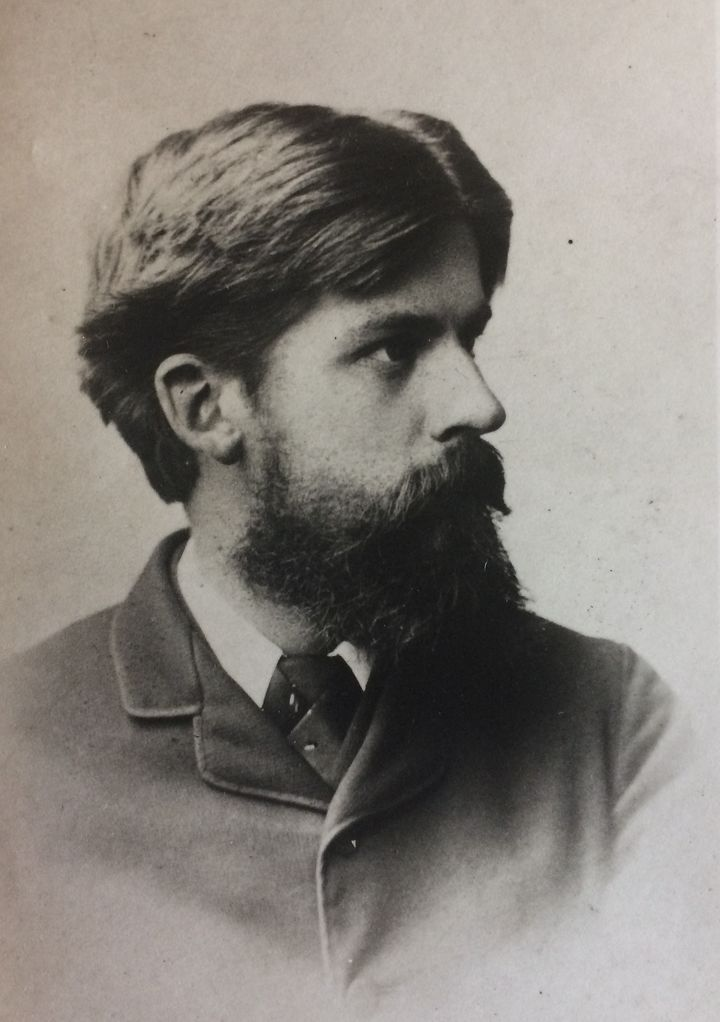 Black and white photographic portrait of a young man in profile, with dark hair and a long dark beard and handsome nose.