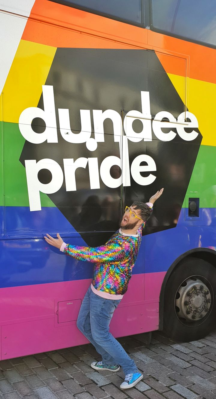"a person in a rainbow-sequined top hugging a bus with their rainbow visual identity on it that says ""Dundee Pride""."