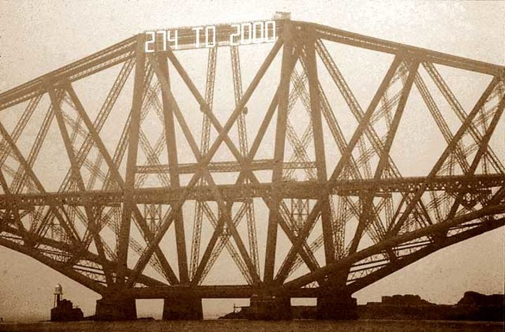 Sepia photograph of the Forth Bridge with a countdown clock attached to its top.