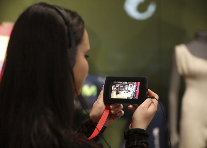 Visitor using a multimedia guide device to watch a film about an object in the Scottish Design Galleries
