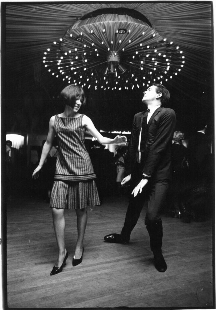Black and white photo of Mary Quant and a man dancing together in a dance hall.