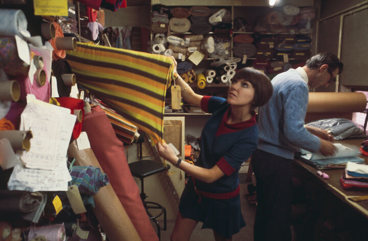 A workshop full of textiles and fabrics with Mary Quant in her trademark black bob pulling fabric off a roll.