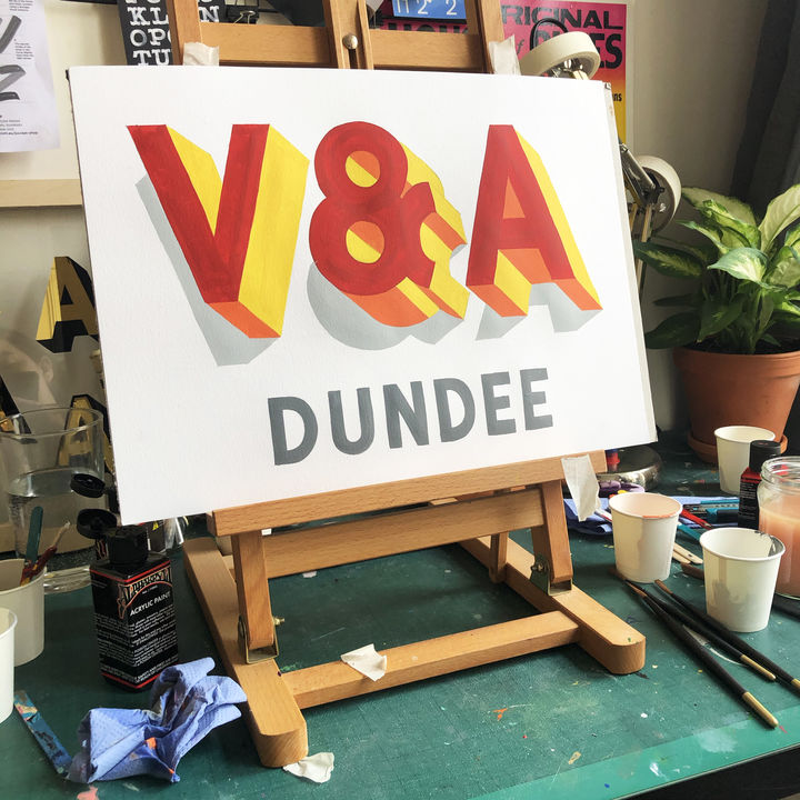 "Photo of a studio set-up with a white paper sign on an easel on which has been painted the words ""V&A Dundee"" in bright lettering."