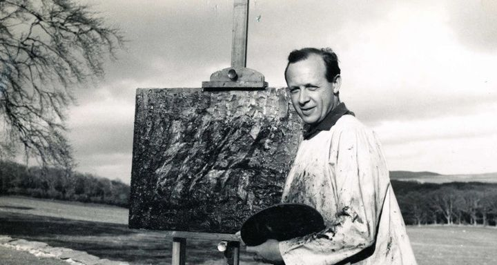 Black and white photo of Bernat Klein in a big smock standing at an easel in the countryside.