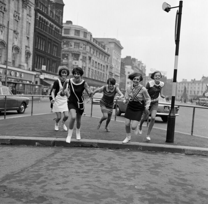 Black and white photo of Mary Quant and a few young women running towards the camera in a street, laughing.