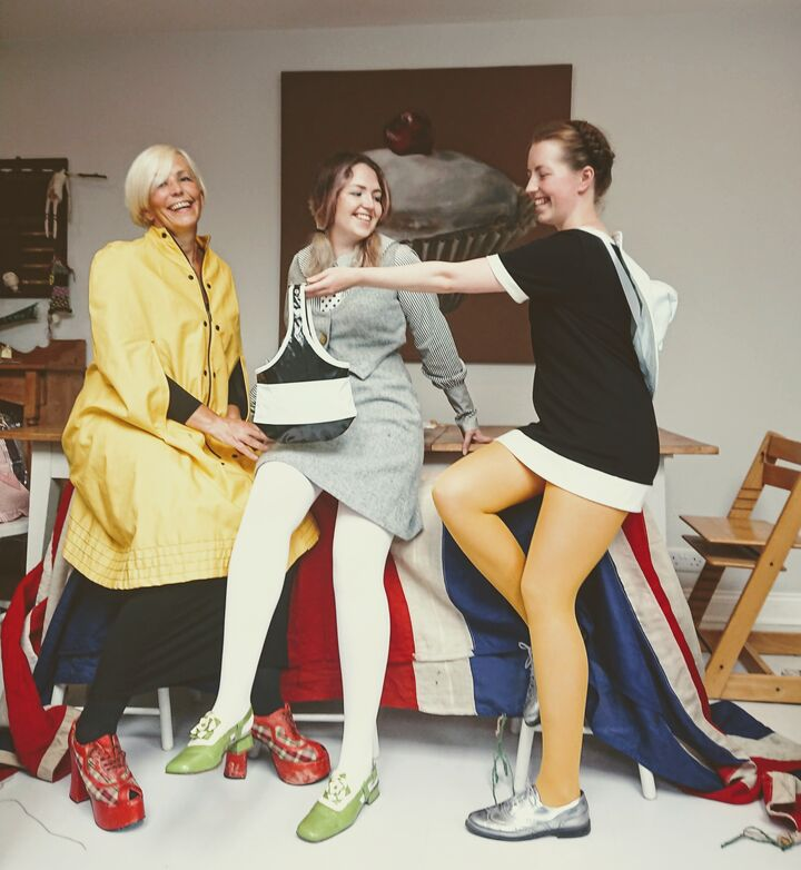 Three women sitting on a table in Mary Quant reproduction outfits.