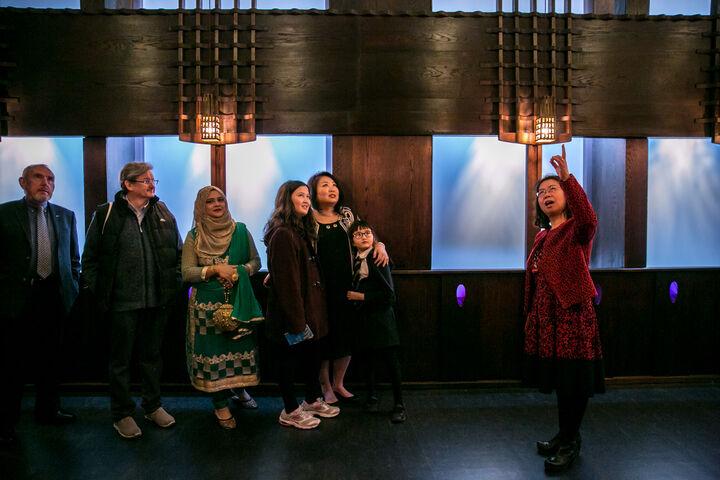 一位女士带领旅行团一行人,站在全部是深色木板和紫色玻璃的麦金托什的橡木厅里。