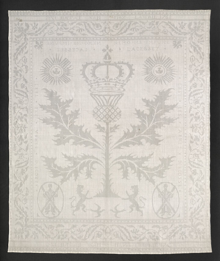 Photo of a fine linen napkin from 1762. It's white and is detailed with thistles and lions embroidered into it.