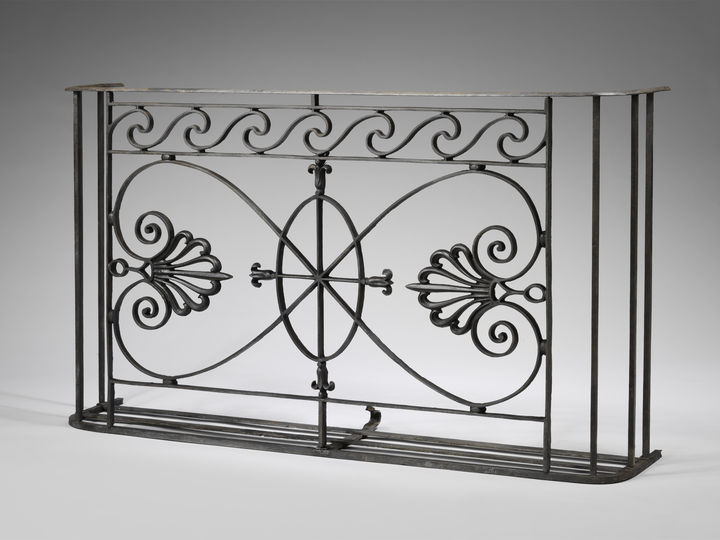 A piece of decorative cast ironwork against a plain background. The balcony piece features heart-shaped outlines and ornamentation resembling palm leaves.