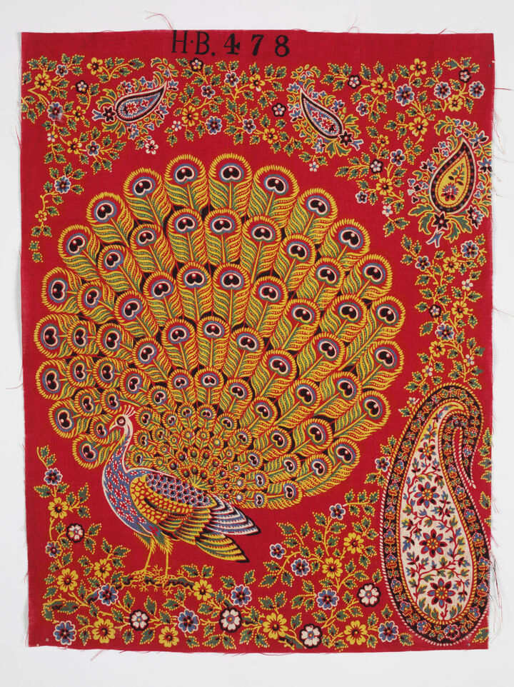 Photo of Turkey Red fabric. it's bright red with an exquisitely embroidered yellow and blue peacock on it, as well as flowers and the Paisley pattern.