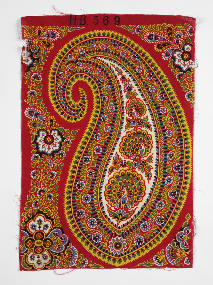 Bright red fabric with intricate yellow and blue paisley pattern on it.