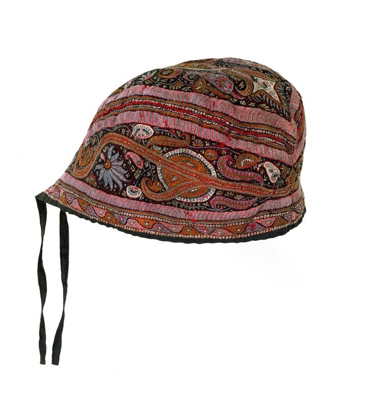 Photo of a Scottish glengarry cap decorated with Indian embroidery in reds and pinks with floral and Paisley motifs.