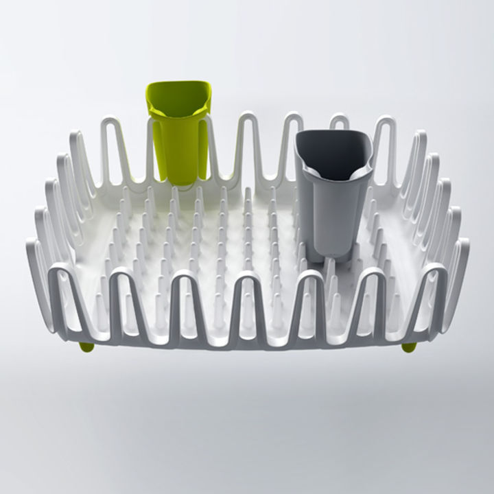 A white dish rack with movable cutlery pots which can be placed on the perimeter to free up space. The clam-like prongs can be used to hang cups and glasses. Spikes in the middle of the rack allow dishes to be stacked in any direction.