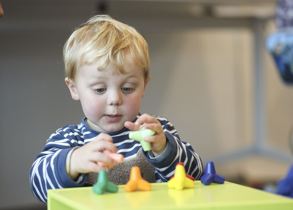 A young boy playing with coloured geometric shapes