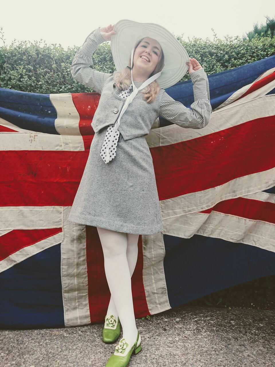 A model wears reproduction Quant attire in front of a union jack flag. The outfit is a grey waistcoat dress.