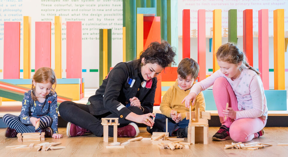 Designer Gabriella Marcella sitting with three children, assembling structures from wooden toy blocks