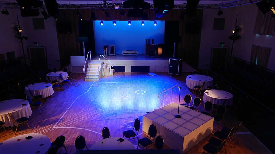 At the back is a stage with several flight cases on it and blue lights shining outwards. A wooden staircase with white handrails connects the stage to the floor in two directions, one towards the camera and one to the right.  The floor is a wooden with white tape marking various lines on the floor.  Towards the front, there is a smaller stage, white with grey lines crossing over.  In the middle of the stage is a microphone stand. Circular tables with white tablecloths and blue dining chairs surround the floor area.