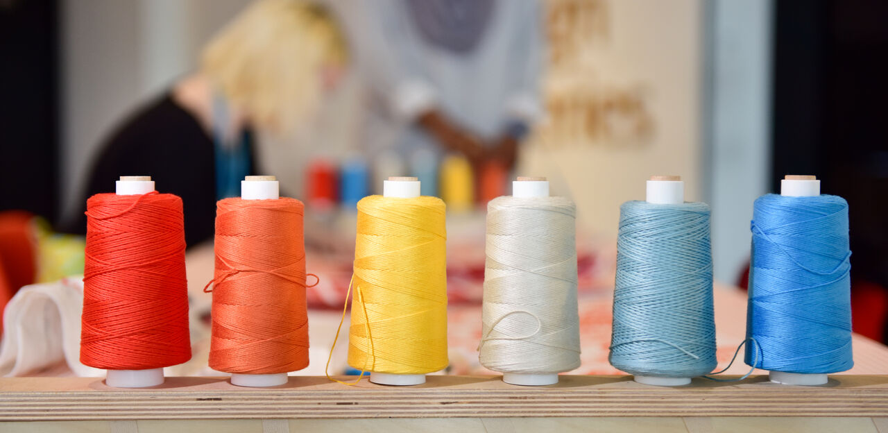Different coloured thread bobbins all lined up in a row.