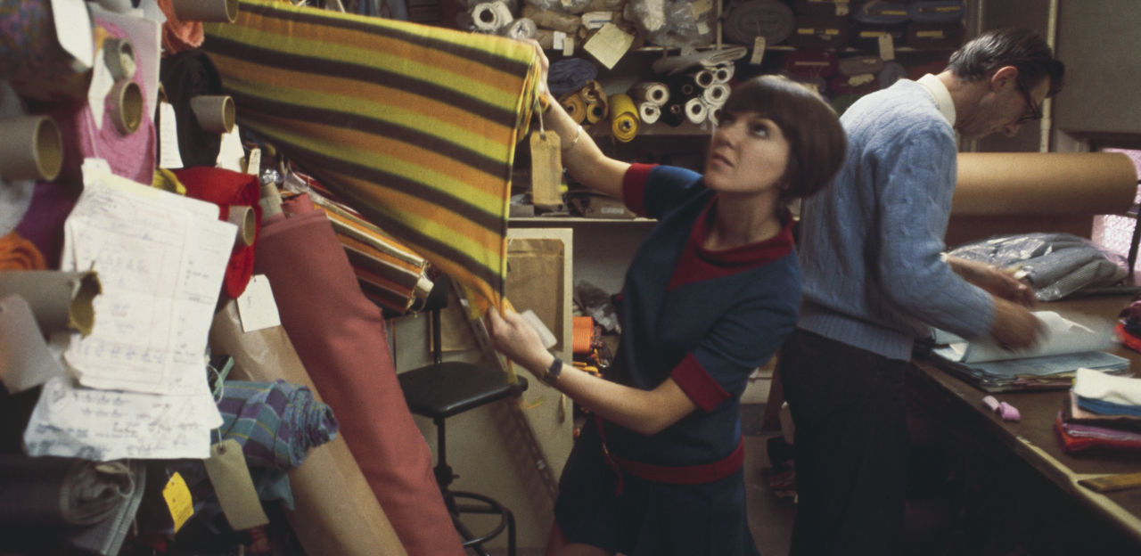 Mary Quant pulling fabric from a wall of samples.