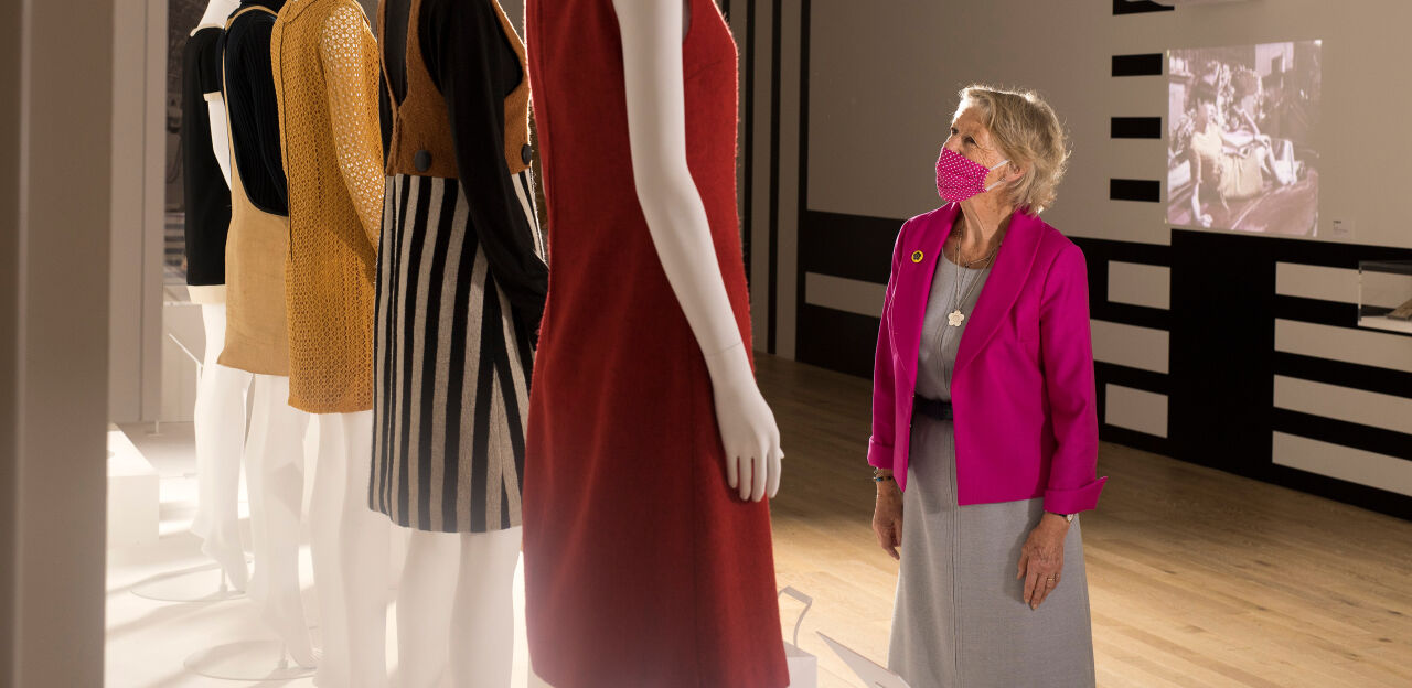 A woman in a fuchsia blazer standing in front of some mannequins wearing Mary Quant clothes.