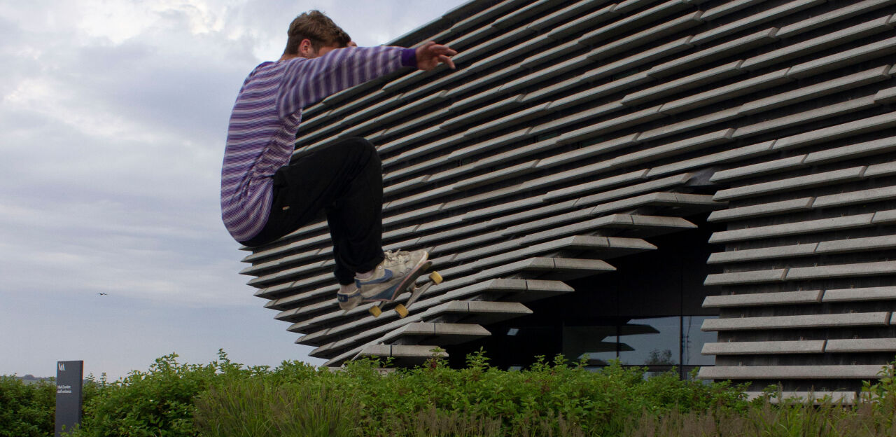 A skater doing a massive leap trick over the furniture next to the benches around V&A Dundee.