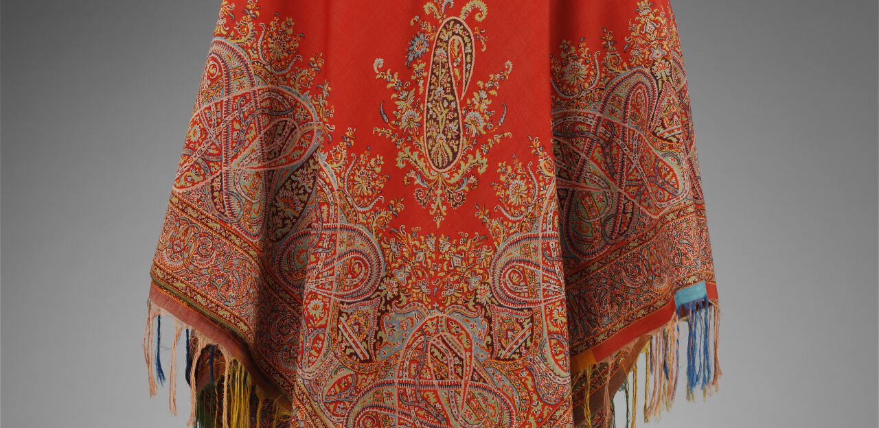 A large red shawl with intricate paisley pattern on it draped over a mannequin.