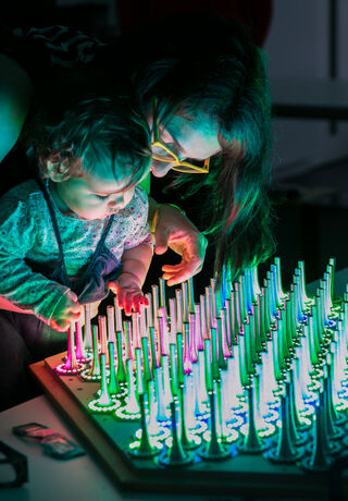 A baby plays with a light-up installation, held by its mother