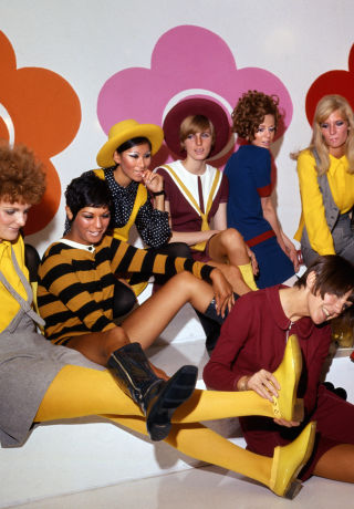 Mary Quant photographed surrounded by models wearing her bright and fun creations.
