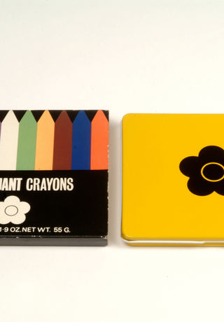 A photograph of 'Mary Quant Crayons', with the coloured crayons on the left, and the tin lid on the right.