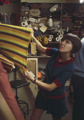 Mary inspecting textiles in a fabric store.