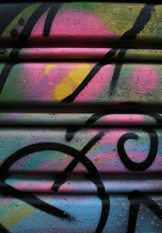 Close-up of a painted street mural in vibrant colours and bold brush strokes or spray lines.