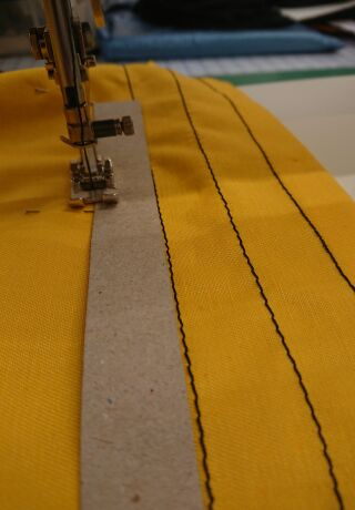 Close-up of a sewing machine working a piece of mustard fabric.