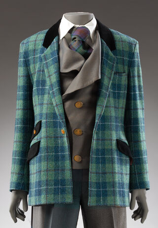 Close-up image of a green and blue Harris Tweed suit jacket with black pockets and brown buttons, and a grey waistcoat